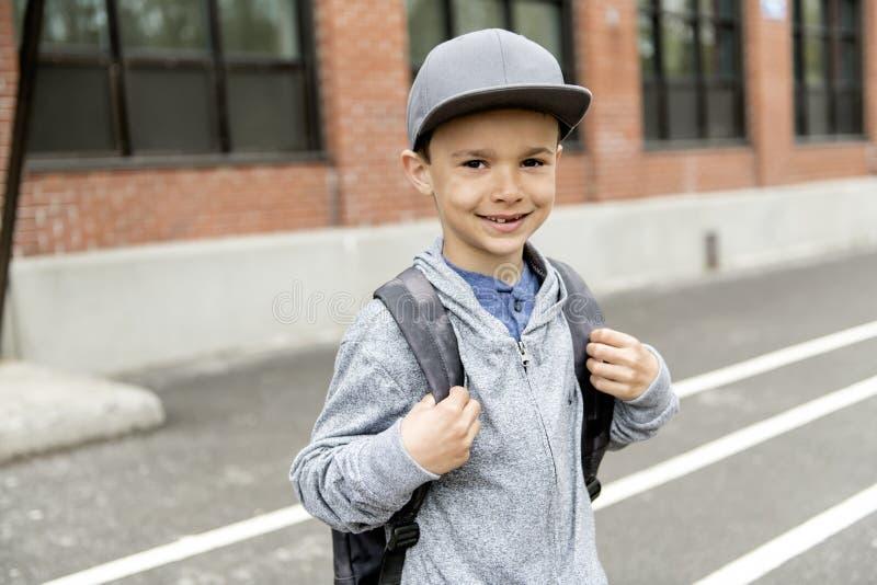 Retrato do menino bonito com a trouxa fora da escola imagens de stock