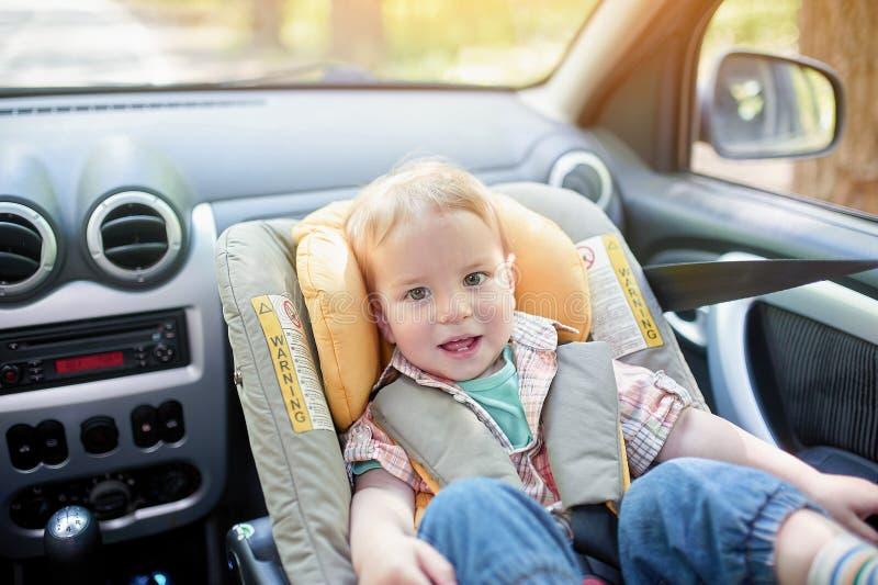 Retrato do menino bonito da criança do bebê de um ano que senta-se no assento da segurança do carro montado no assento dianteiro  fotos de stock