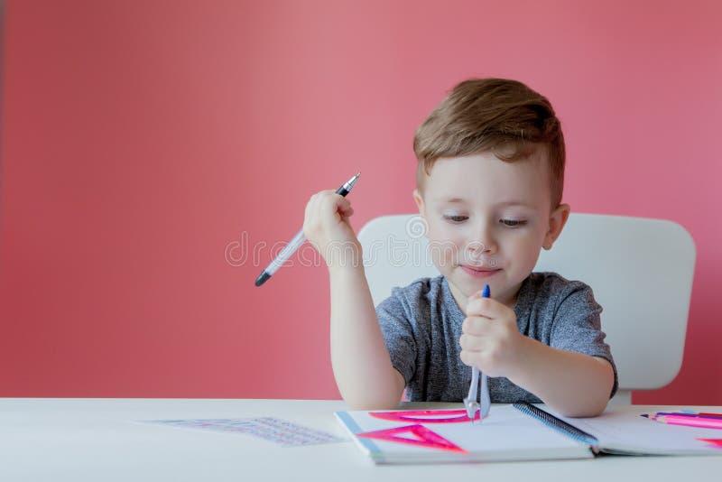 Retrato do menino bonito da criança em casa que faz trabalhos de casa Pouco criança concentrada que escreve com lápis colorido, d foto de stock