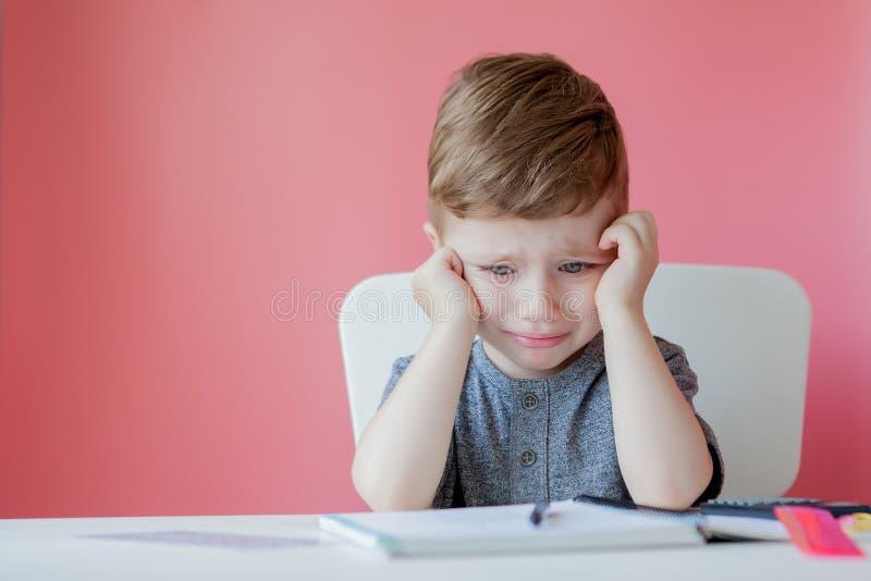 Retrato do menino bonito da criança em casa que faz trabalhos de casa Pouco criança concentrada que escreve com lápis colorido, d imagem de stock