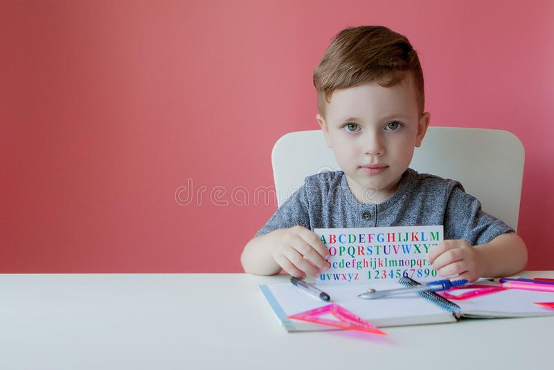 Retrato do menino bonito da criança em casa que faz trabalhos de casa Pouco criança concentrada que escreve com lápis colorido, d fotografia de stock royalty free