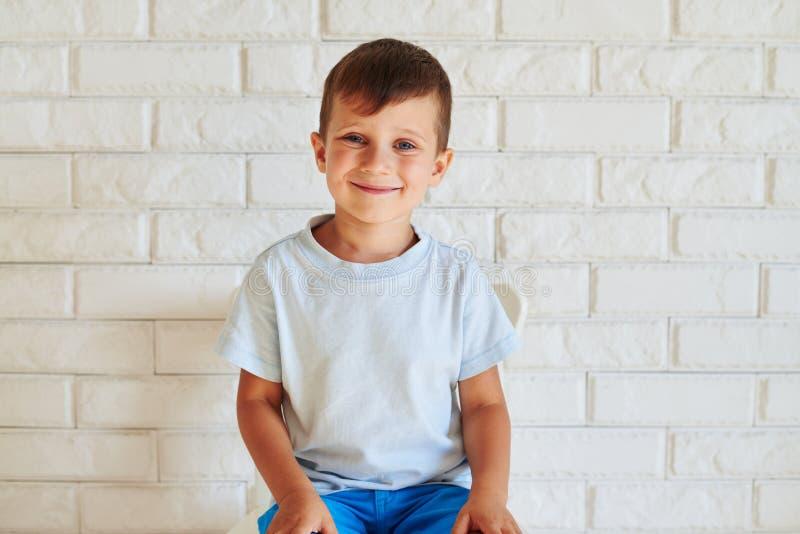 Retrato do menino bonito de sorriso que senta-se na cadeira contra bric branco fotos de stock royalty free