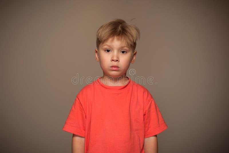 Retrato do menino bonito pequeno com a cara triste, pensativa fotografia de stock royalty free