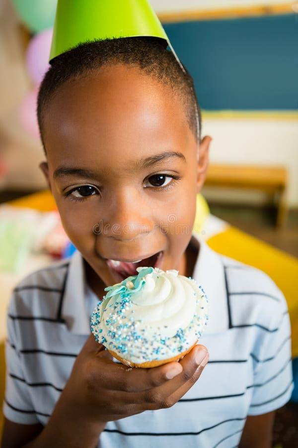 Retrato do menino bonito que come o queque durante a festa de anos imagem de stock
