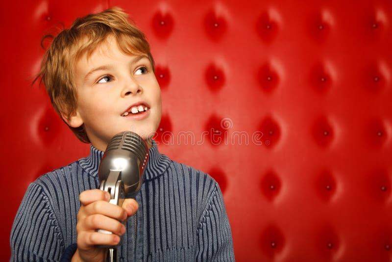 Retrato do menino com o microfone na cremalheira foto de stock royalty free
