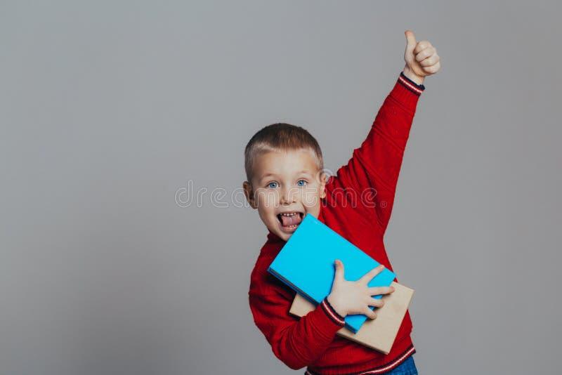 Retrato do menino de sorriso atrativo em uma camiseta vermelha com close-up dos livros fotografia de stock
