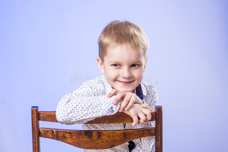 Retrato do menino de sorriso bonito na cadeira foto de stock royalty free