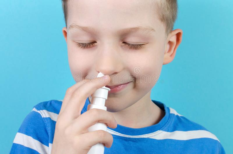 Retrato do menino de sorriso com pulverizador nasal, fundo azul imagens de stock