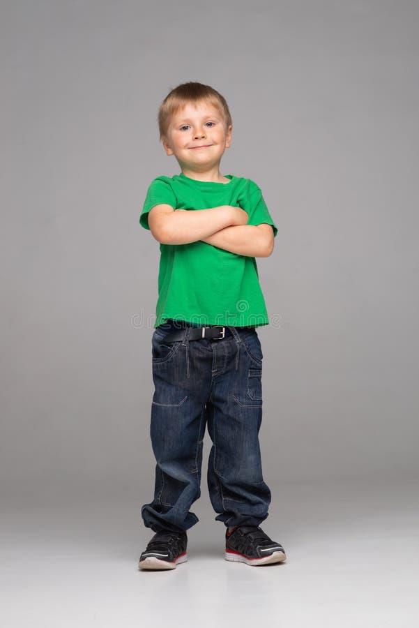 Retrato do menino de sorriso feliz no t-shirt e em calças de brim verdes Criança atrativa no estúdio fotos de stock