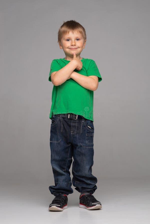 Retrato do menino de sorriso feliz no t-shirt e em calças de brim verdes Criança atrativa no estúdio imagens de stock royalty free
