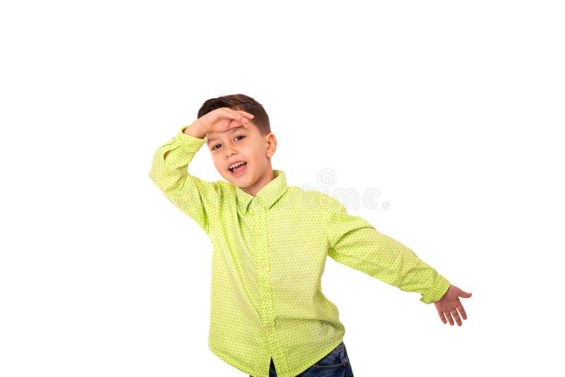 Retrato do menino de sorriso que veste a camisa amarela, isolado Mostra com seu gesto de mão que é um super-herói fotografia de stock