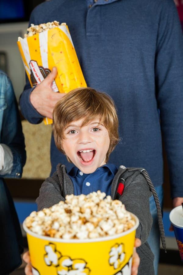 Retrato do menino entusiasmado que mostra a pipoca no cinema fotografia de stock royalty free