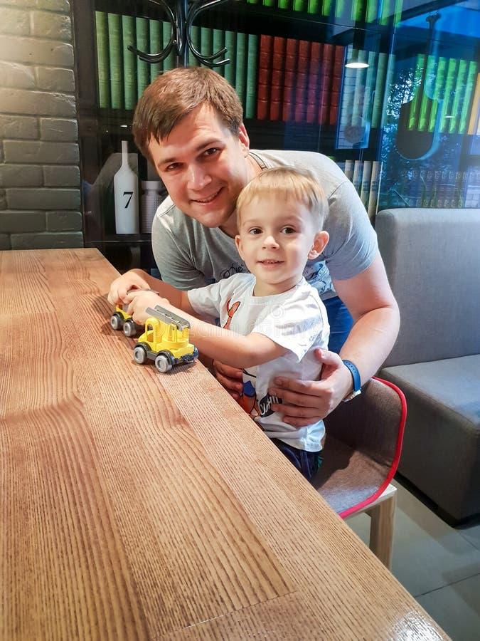 Retrato do menino feliz da crian?a que joga com seu pai com brinquedos pl?sticos ao sentar-se atr?s do counterdesk no caf? imagens de stock royalty free