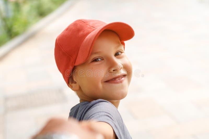 Retrato do menino feliz no tampão que guarda o sorriso e guardar a mão fotos de stock royalty free