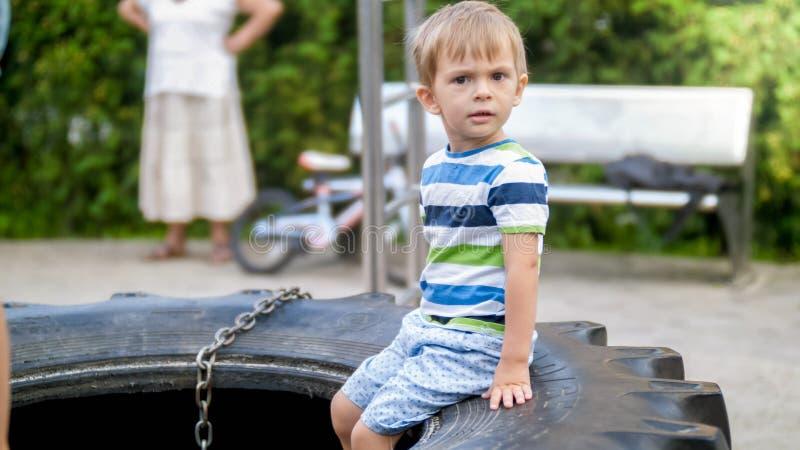 Retrato do menino idoso da criança de 3 yeas witting no pneu de borracha grande no campo de jogos das crianças no parque imagem de stock
