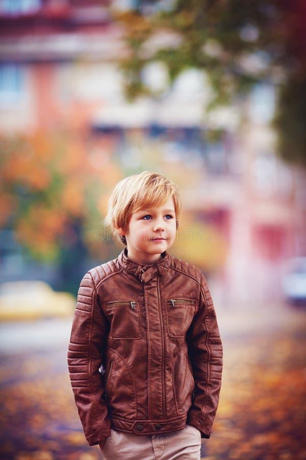 Retrato do menino novo de sorriso, criança que anda no parque da cidade do outono entre as folhas caídas foto de stock royalty free