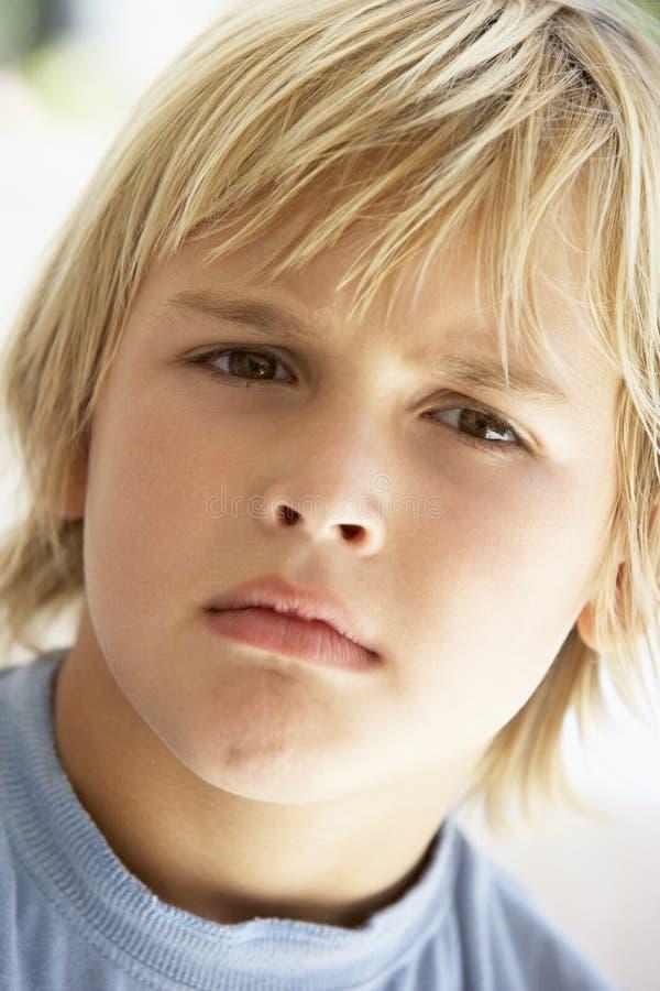 Retrato do menino novo que olha de sobrancelhas franzidas fotografia de stock royalty free