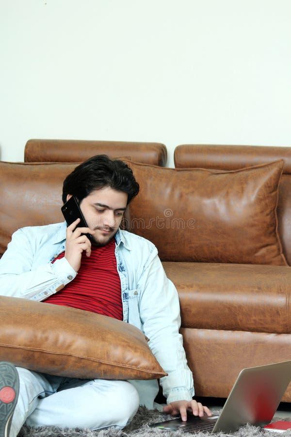 Retrato do menino novo que senta-se no assoalho com telefone de fala e que usa o portátil fotos de stock royalty free