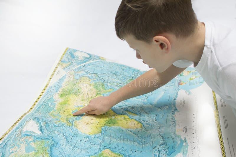 Retrato do menino pequeno que estuda o mapa do mundo fotos de stock