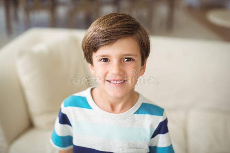 Retrato do menino que está o sofá próximo na sala de visitas foto de stock royalty free