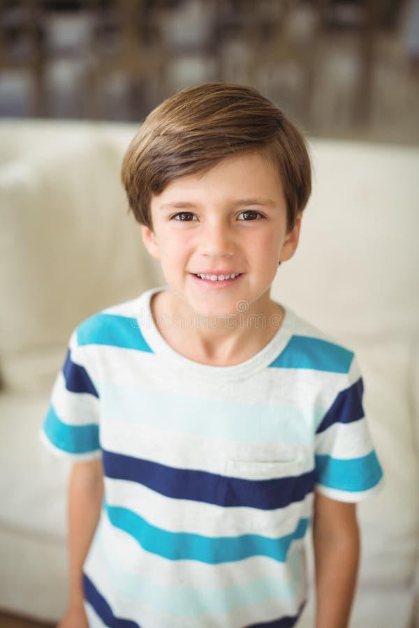 Retrato do menino que está o sofá próximo na sala de visitas imagens de stock