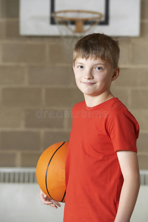Retrato do menino que guarda o basquetebol no Gym da escola fotografia de stock