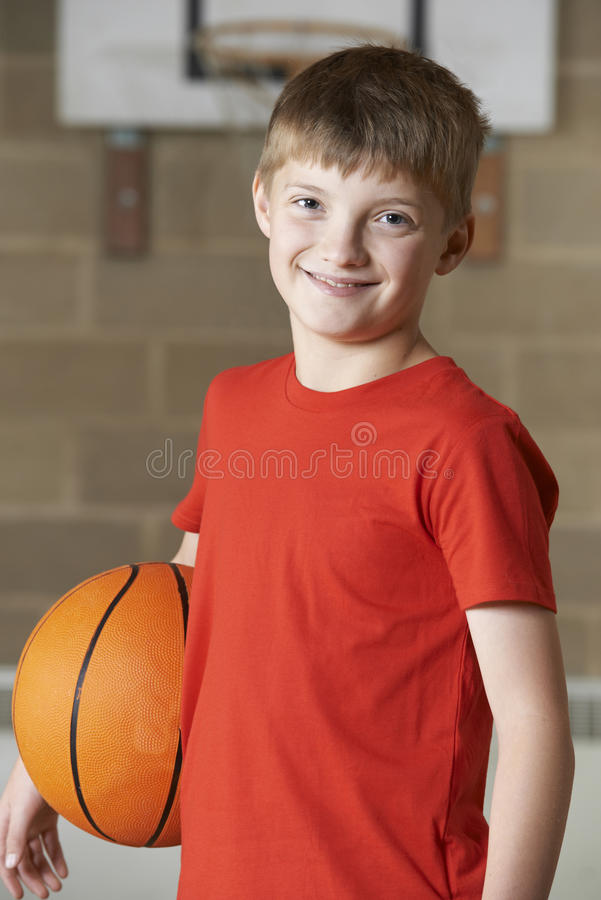 Retrato do menino que guarda o basquetebol no Gym da escola imagem de stock