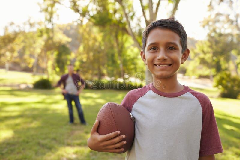 Retrato do menino que guarda o futebol no parque, paizinho no fundo fotografia de stock royalty free