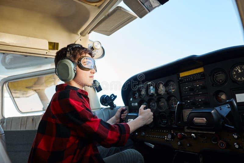 Retrato do menino que olha focalizado e sério, sentando-se na cabina do piloto do avião pequeno fotos de stock royalty free