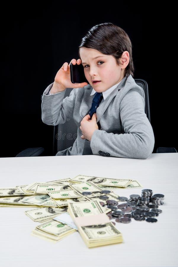 Retrato do menino seguro que joga o homem de negócios e que fala no smartphone foto de stock
