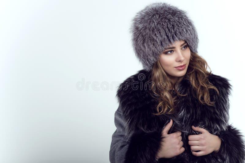 Retrato do modelo de sorriso bonito novo que veste o chapéu forrado a pele e o revestimento na moda de raposa da malha imagem de stock