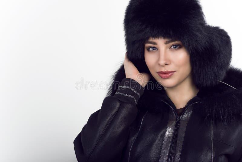 Retrato do modelo de sorriso bonito novo que veste o chapéu forrado a pele fechado de couro preto na moda do revestimento e da zi fotografia de stock