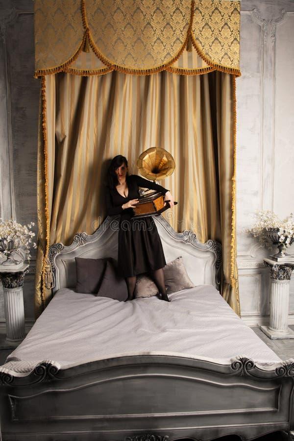 Retrato do modelo fêmea bonito novo na posição 'sexy' preta do vestido na cama dentro com o estúdio interior do gramofone fotografia de stock royalty free