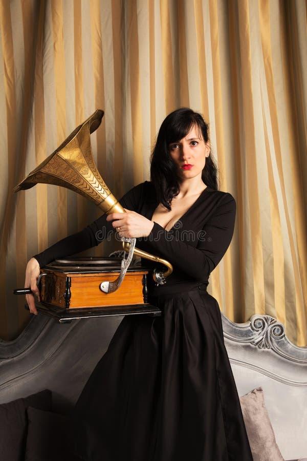 Retrato do modelo fêmea bonito novo na posição 'sexy' preta do vestido na cama dentro com o estúdio interior do gramofone fotos de stock royalty free