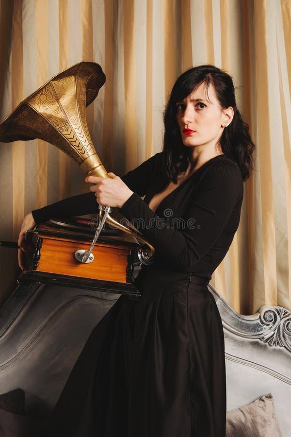 Retrato do modelo fêmea bonito novo na posição 'sexy' preta do vestido na cama dentro com o estúdio interior do gramofone fotos de stock