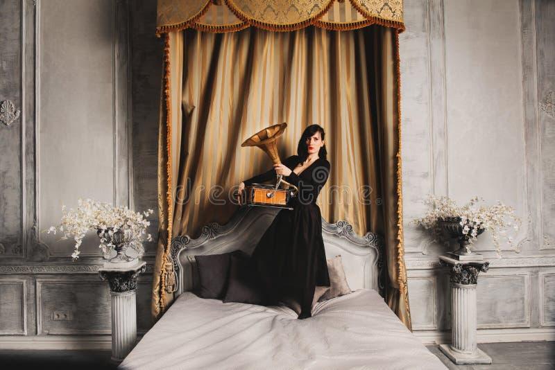 Retrato do modelo fêmea bonito novo na posição 'sexy' preta do vestido na cama dentro com o estúdio interior do gramofone foto de stock royalty free