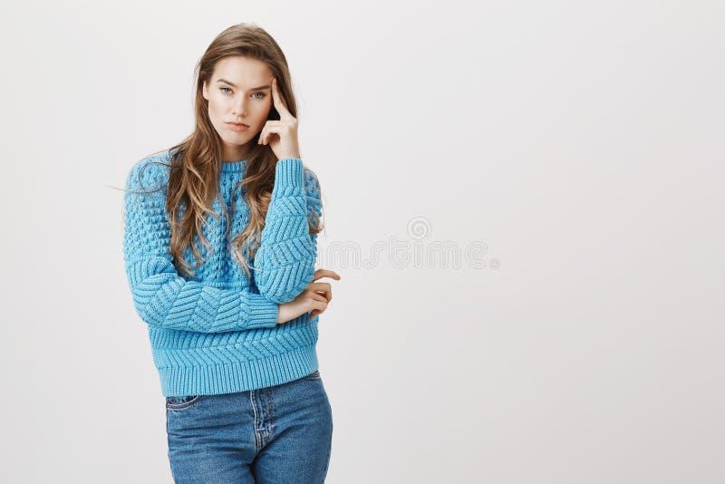 Retrato do modelo fêmea caucasiano furado incomodado, guardando a mão no templo e expressando o desagrado e o aborrecimento com c foto de stock
