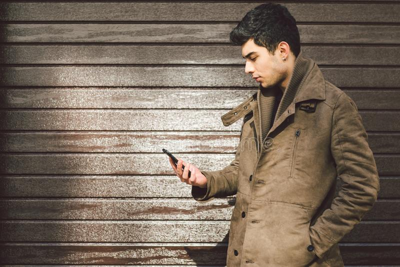 Retrato do modelo masculino turco considerável novo da morena mediterrânea da raça no revestimento de couro usando o telefone  fotografia de stock