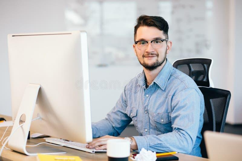 Retrato do moreno do oung nos glasess e em um funcionamento azul da camisa com um computador em seu desktop no escritório É imagens de stock
