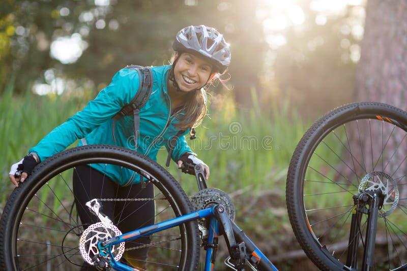 Retrato do motociclista fêmea que repara o Mountain bike imagens de stock royalty free