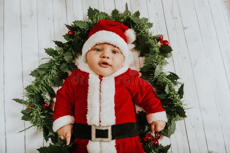 Retrato do Natal do bebê recém-nascido adorável que veste o equipamento do ` de Santa Claus imagem de stock royalty free