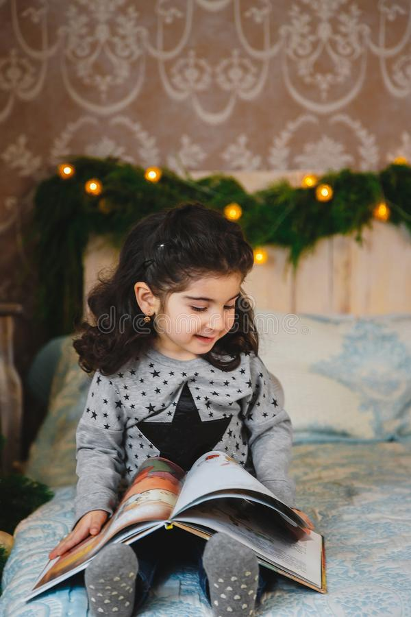 Retrato do Natal da menina bonita de sorriso feliz que senta-se na cama, livro de leitura sob a árvore de Natal Feriado de invern fotografia de stock royalty free