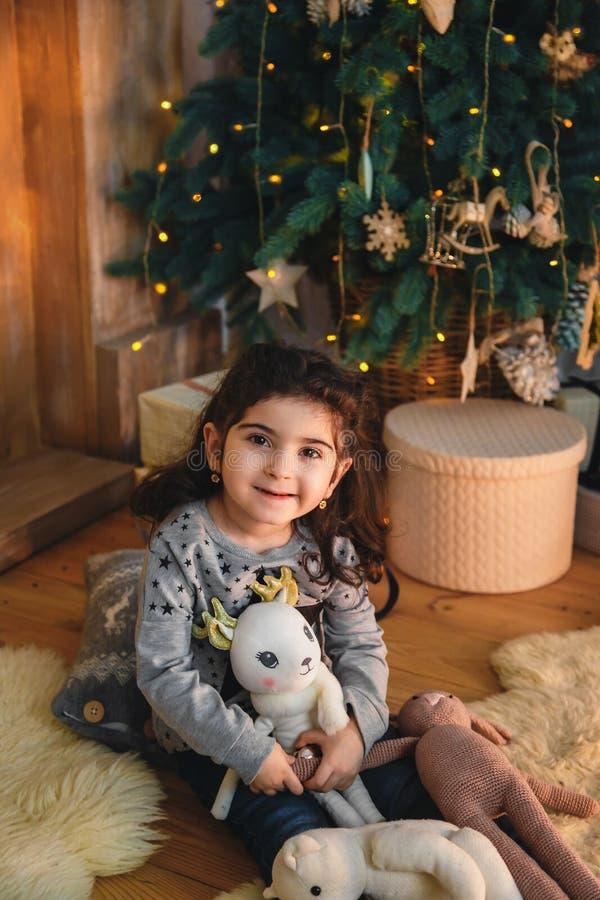 Retrato do Natal da menina bonita de sorriso feliz que senta-se no assoalho com presentes sob a árvore de Natal Feriado de invern imagens de stock