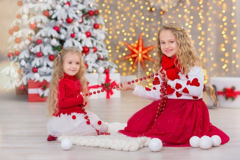Retrato do Natal de dois amigos de sorriso das irmãs das meninas bonitos beautyful e da árvore branca verde luxuosa do xmas no es imagem de stock