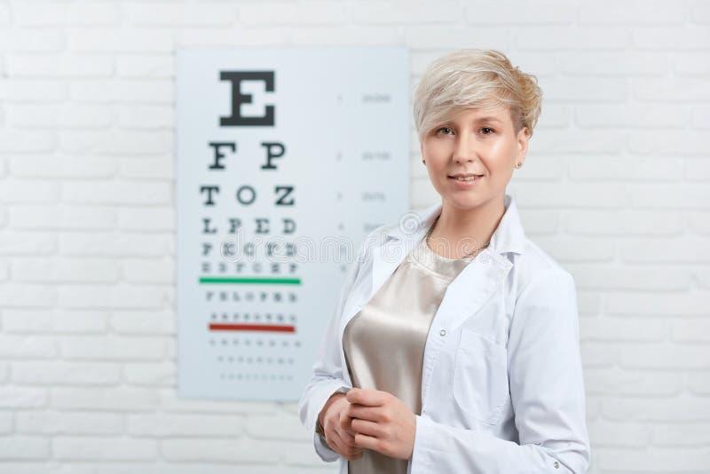 Retrato do oftalmologista que fica na frente da tabela da inspeção visual fotos de stock