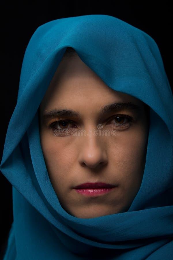 Retrato do Oriente Médio da mulher que olha triste com o artista azul do hijab fotografia de stock