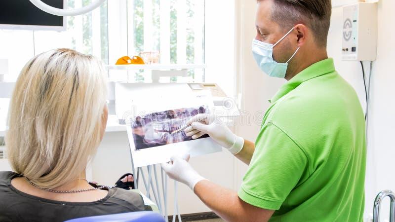 Retrato do orthodontist que mostra problemas nos dentes a sua imagem de utilização paciente do raio X foto de stock