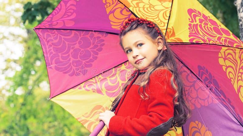Retrato do outono da menina agradável no revestimento vermelho com o guarda-chuva colorido nas mãos Dia ensolarado do outono Core fotos de stock