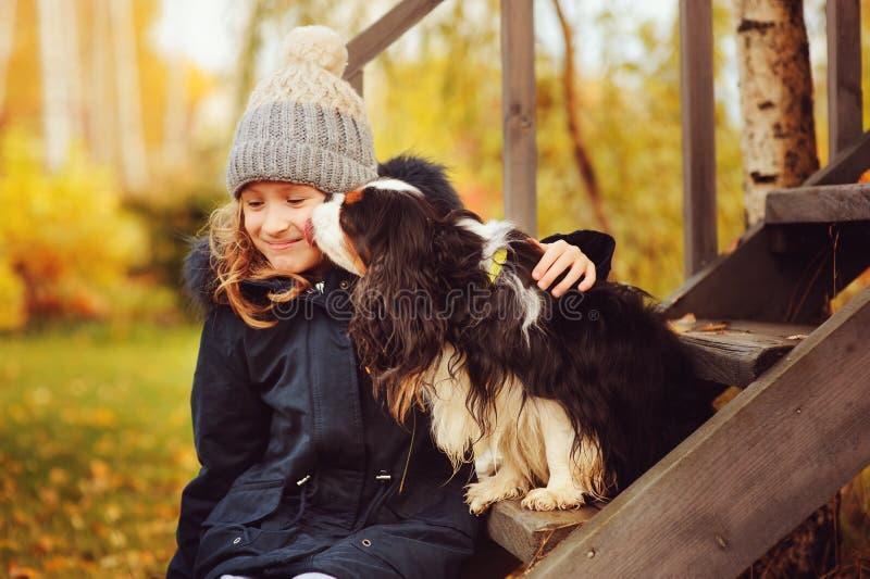 Retrato do outono da menina feliz da criança que joga com seu cão do spaniel no jardim imagens de stock