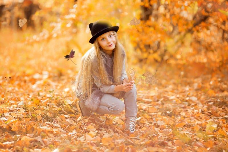 Retrato do outono de uma menina bonito no chapéu Menina 8 anos de caminhadas velhas no parque do outono imagem de stock royalty free